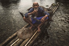 Cormorant fisherman.. (Syahrel Azha Hashim) Tags: portrait nikon expression water mountains tokina shallow holiday simple elder bambooraft chinese 16mm portraiture xingping ultrawideangle hat liriver traditionalclothing humaninterest paddle river splashes traditional dof bokeh bamboo touristattraction single guilin conventional unique getaway handheld streetphotography iconic vacation destination china light culture naturallight moment colorful fishing cormorants travel syahrel street detail colors uwa d300s beard oldman fisherman