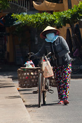 hoi an-5467 (yukkycakes) Tags: bike bicycle lady walking colorful basket bright laden unescoworldheritagesite vietnam thongs spotty multicolored goodies dotty pointyhat facemask coveredface fashionfauxpas hian ancientcity conicalhat spottypants nnl southcentralvietnam quangnamprovince pushingbike southchinaseacoast peacefulmeetingplace dottypants thongswithsocks
