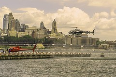 Helicopter Landing In Downtown Helipad (people are loading on another flying machine for a sightseeing trip around Manhattan Island) (nrhodesphotos(the_eye_of_the_moment)) Tags: dsc06478160 theeyeofthemoment21gmailcom wwwflickrcomphotostheeyeofthemoment people sightseeing tourists eastriver waterfront brooklyn manhattan nyc reflections shadows transportation helicopter helipad downtownmanhattan buildings architecture pylon metal glass skyline clouds sky road highway cars trees overpass flying machine outdoor urban