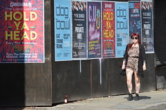 Hold Ya Head, Thomas Street, Northern Quarter, Manchester, England. (westport 1946) Tags: england unitedkingdom manchester manchesterstreets streetphotography thomasstreet northernquarter streetview citylife cityview cityscene streetscene urbanscene pedestrian female women girl pavement sidewalk outdoor posters clubposters adverts streetposters streetadvertising thebunker caingrain theliarslounge bottleofbeer holdyahead dogbowl tottoe tattoos smoking