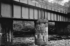 Former Railway Bridge, Craigellachie (PalletTownHero) Tags: uk bridge church station shop bar forest 35mm scotland highlands pub woods ilfordhp5 400 fujifilm ilford olympustrip35 moray thomastelford victoriabridge aberlour expiredfilm speyside glenlivet grampian craigellachie themashtun glenfarclas banffshire marypark riverspey josephwalker gnsr gnosr