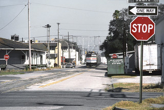 Amtrak Silver Star, led by EMD F40PHR locomotive # 385, is seen in the distance heading southbound down East Street as it rolls toward the old SAL freight station in downtown Clearwater, Florida, on Sunday morning 1-29-1984