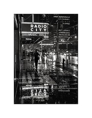 nyc#96 - A Rainy Night On 6th Avenue (Nico Geerlings) Tags: ngimages nicogeerlings nicogeerlingsphotography nyc ny usa us newyorkcity manhattan midtown rain rainy raining umbrella reflection reflections 6thave 6thavenue avenueoftheamericas radiocitymusichall streetphotography leicammonochrom 50mm summilux