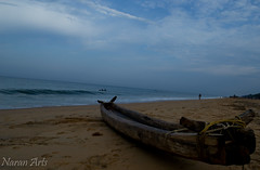 In Oblivion or Reminiscing ! (Aravind Bee) Tags: blue sea sky art beach nature boat solitude waves tide wave canoe shore lone lonely aravind seashore naranarts