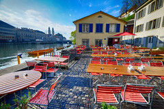 Riverside Cafe in Zurich, Switzerland (` Toshio ') Tags: toshio zurich switzerland europe european limmat limmatriver grossmunster river church restuarant chairs tables fujixe2 xe2