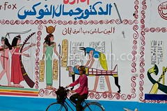 tourist woman on a bicycle, paintings on the walls of GOURNA village in Thebes  Louxor - Egypt    ///  , touriste femme, peintures et dessin sur les maison du village de GOURNA a Thebes  Louqsor - Egypte (setboun photos) Tags: africa woman streetart art bike bicycle shop architecture female shopping bicycling store magasin commerce femme transport egypt cycle boutique pharaoh bicyclist antiques luxor bicyclette trade murales velo egypte cycliste artmural afrique pharaonic pharaon muralpainting petitcommerce muralart twowheels louxor peinturemurale antiquite smallbusiness touristshop antiquites nilevalley louqsor egyptianculture deuxroues artdesrues arabcountry smalltrade faireduvelo paysarabe ecologicaltransport littletrade cultureegyptienne culturepharaonique pharaonicculture claudinech friendsofs valleedunil valledesrois valleyofthekingsandthequeens gournahvillage magasinpourtouristes