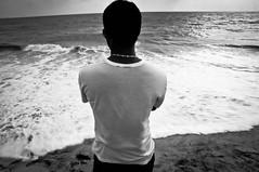 海を眺め頭を冷やして冷静に考える男性