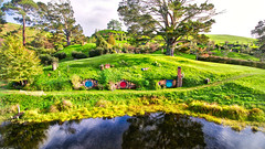 Over The Pond In Hobbiton (Stuck in Customs) Tags: hobbiton newzealand northisland stuckincustomscom treyratcliff treyratcliffcom matamata waikato nz ratcliff trey horizontal houses hobbit lordoftherings lotr pub greendragoninn inn colour color outside outdoor outdoors mirror reflection lake pond water light glowing underground trees blue purple white black orange green yellow hills rolling rr dailyphoto sony ilce7r may 2016 p2016 dji fc330 drone quadcopter quad home
