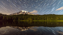 """ At the speed of light, the body shrinks to zero and time stands still."" (Brendinni) Tags: rainier mountrainiernp reflection reflections stacked stars startrails tress landscape water moonlit clouds quotes alberteinstein"