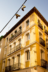 Bright balconies and shoes (G.Roca) Tags: sunny building window street city angular shoes shadows summer spain outdoors afternoon diagonal madrid architecture yellow balcony hangingshoes