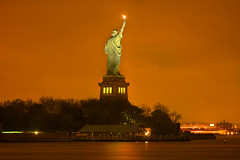 Liberty Lights Up the Sky (SunnyDazzled) Tags: sky newyork reflection water fog night clouds lights freedom glow atmosphere unesco worldheritagesite torch lighttrails statueofliberty libertyisland pedastal