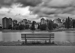 A Moody Afternoon... (Claire Chao) Tags: longexposure light sky blackandwhite bw canada water vancouver canon bench 50mm lightandshadows moody cityscape quiet afternoon waterfront cloudy britishcolumbia overcast falsecreek englishbay driftingclouds shape westend silky 2012 longexposures vanierpark downtownvancouver movingclouds beautifulbritishcolumbia 50mmf12 canonllens westendvancouver silkywater springintosummer canoneos5dmarkii clouddance clouddancing canon50mmllens