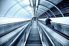 Down in the tube station at midday (Pat Charles) Tags: london england unitedkingdom uk metro underground travel transport tourism stairs staircase escalator leadinglines perspective disappearingpoint journey monochrome future futuristic nikon interior indoor inside architecture