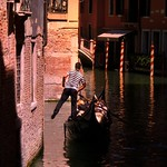 A singing gondolier kicks off wall through the canals of Venice