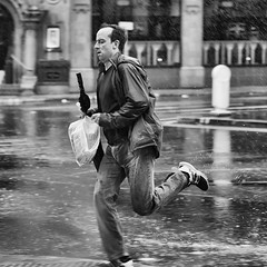 Glad I brought the brolly (Mister Oy) Tags: davegreen oyphotos oyphotos manchester rain rainy weather run running mono monochrome blackandwhite fujixpro2 fuji56mmf12 fujinon56mmf12 street streetphotography wet rush rushing busy late hurry hasten