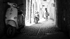 Run, baby, run (Thomas Demeulemeester) Tags: dem 2016 bw blackwandwhite bokeh nb noiretblanc rodos running street streetphotgraphy vespa bnw canon600d child day dehors ef50mmf18ii enfant hautcontraste highcontrast holidays journe juillet july murs oldtown outdoors pavement ruelle streetphotographie summer vacances walls t vieille ville