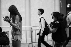 Life in Motion - The tech duo... (EHA73) Tags: aposummicronm1290asph leica leicamm hongkong streetphotography travel monochrome blackandwhite bw timessquare central people crowd smartphones typ246