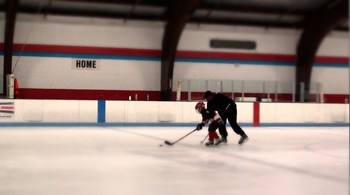 Brad Perry teaching a hockey player to skate with the puck at a hockey clinic