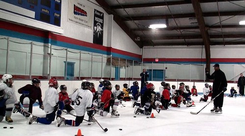 Brad Perry coaching a full group of players at a hockey school in Chicago