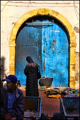 Stopping at the Blue Door (David K. Edwards) Tags: blue shopping clothing paint market bricks clothes morocco essaouira bluedoor garments fabrics assuwayrah iqeaterhat