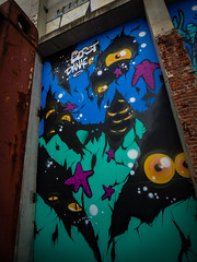 They Dwell in the Corners (Steve Taylor (Photography)) Tags: art cartoon graffiti mural streetart building container wall black blue green mauve purple yellow orange scary eerie frightening spooky weird odd strange mad brick metal newzealand nz southisland canterbury christchurch cbd city perspective starfish alien monster eye crack split fissure berst danae halo bobbyhung isaac theatre theater royal
