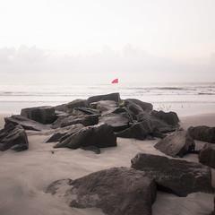 (gwoolston) Tags: rocks jetty ocean seashore sand jerseyshore stoneharbor flag birds waves