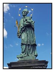 Saint John of Nepomuk, Charles Bridge, Prague (Doyle Wesley Walls) Tags: lagniappe 2136 statue clouds christianity religion religiousfigure bluesky saintjohnofnepomuk charlesbridge pragueczechrepublic iphonephoto smartphonephoto doylewesleywalls crucifix