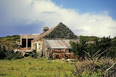 Farm with lobster traps - Cape Clear Island, Cork, Ireland.. (edk7) Tags: nikkormat ft2 slide edk7 197806 eire ireland cape clear island cléire farm farmhouse lobster traps m627 architecture building oldstructure barn shed fieldstone cloud sky 1978