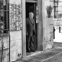 """Would you like postcards, a sword ?"" (halifaxlight) Tags: street door bw man shop square spain toledo postcards swords oldcity shopkeeper malinconiamelancholy blinkagain bestofblinkwinners"