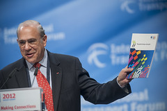 Angel Gurría holds up an OECD study at the Annual Summit