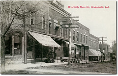West side of Main Street, Wolcottville, Indiana (Hoosier Recollections) Tags: horses people usa signs man men history buildings walking advertising awning hardware clothing cafe furniture restaurants indiana streetscene bicycles transportation drugs shops pedestrians storefronts banks businesses barbers lagrangecounty wolcottville hoosierrecollections