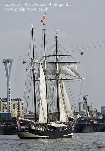 The Dutch 3 masted topsail schooner Oosterschelde from Rotterdam passing the new cable car in London on 25th July 2012 as part of the tall ships Avenue of Sail parade.