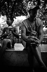 The Drug Addict and the Tourist (stimpsonjake) Tags: nikoncoolpixa 185mm streetphotography bucharest romania city candid blackandwhite bw monochrome tourist drugaddict homeless child boy man