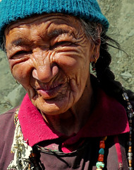 Ladakhi Woman (Jo Pye) Tags: old travel shadow summer portrait people woman sun india mountains detail travelling smile face hat lines sunshine smiling closeup trekking trek walking happy lumix person necklace beads eyes women asia hiking expression walk turquoise character buddhist traditional photojournalism traditions tribal hike panasonic jewellery traveller backpacking elderly elder local earrings braids kashmir tribe backpacker emotions leh selling wrinkles himalayas folds plaits apricots ladakh kashmiri indigenous 2012 braided plaited creases ladakhi crinkled gh2 jopye