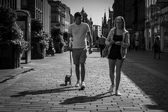 Puppy Love (Leanne Boulton) Tags: monochrome outdoor urban street candid portrait streetphotography candidstreetphotography streetlife eyecontact candideyecontact man male woman female boy girl face faces couple facial expression love romance puppy dog walking pet animal backlit tone texture detail depth perspective natural light shade shadow city scene human life living humanity people society culture canon 7d black white blackwhite bw mono blackandwhite glasgow scotland uk
