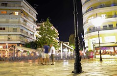 Meet you here again (kutruvis nick) Tags: greece greek hellas chalkis streetphotography people longexposure pedestrianwalkway buildings trees shops cafes chairs tables night lights poles nik kutruvis nikon d5100