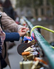Putting a Lock on the Pont near Notre Dame in Paris (Kalexander2010) Tags: bridge people paris france photography leute lock flag streetphotography americanflag locks peuple padlocks travelphotography capitalcity lovelocks thestreetsofparis kalexander lesruesdeparis kalexanderphotography