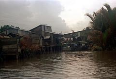 33-573 (ndpa / s. lundeen, archivist) Tags: nick dewolf nickdewolf 33 reel33 color photographbynickdewolf 1970s 1972 fall film 35mm winter 1973 asia vietnam southvietnam vietnamese southvietnamese saigon river saigonriver riverlife watersedge riversedge building buildings house houses home homes stilts onstilts elevated builtonstilts boat boats powerlines