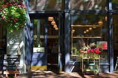Buds And Baked Goods (MPnormaleye) Tags: shop store bakery florist floral flowers basket cart window reflection glass urban city utata 24mm street neighborhood