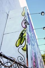 Kenny Scharf sneaking out from under Lady Aiko (damonabnormal) Tags: street city nyc newyorkcity urban streetart graffiti fuji manhattan streetphotography september urbanart aerosol 2012 thebigapple urbanite kennyscharf x100 ladyaiko fujix100