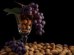 P1050856_001 (Aggelos Delis) Tags: almonds grapes bunch glass stilllife