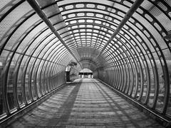Footbridge at the Poplar DLR station, London, UK (Roman's pixels) Tags: poplardlrstation poplar poplarstation perspective footbridge london canarywharf bw blackwhite blackandwhite monochromic architecture england uk unitedkingdom romanspixels x100t fuji silverefexpro
