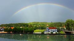 Rainbow (blondinrikard) Tags: regnbåge rainbow outthewindow windowreflection openwindow houses flagpoles marklandsgatan rays light sky