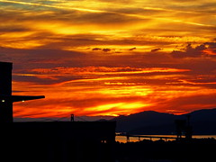 Last night's blazing departure (peggyhr) Tags: peggyhr sunset silhouettes ocean lionsgatebridge lights building clouds sky orange purple yellow red black dsc00854a vancouver bc canada level1photographyforrecreation
