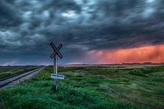 Train Runs Daily (ScottBennie) Tags: landscape storm nature clounds saskatchewan rural prairie sunset scenery outside canon2470f28 crossing roadtrip canada sky green traintracks movingclouds red gray