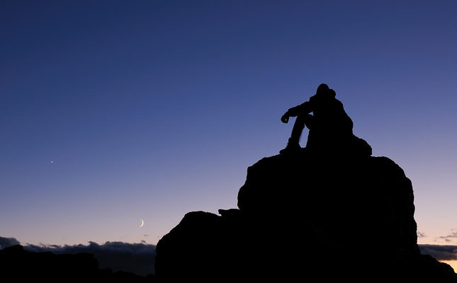 Climber on a mountain peak in the Rocky Mountains of Colorado, under a night sky