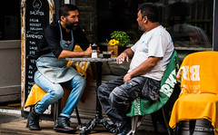 2016 - Baltic Cruise - Copenhagen - Cafe Chat (Ted's photos - For Me & You) Tags: 2016 balticcruise tedmcgrath tedsphotos copenhagen denmark smoker smoking denim denimjeans cropped vignetting cafe table seating seated sitting males two duo reflection menu beard streetscene people