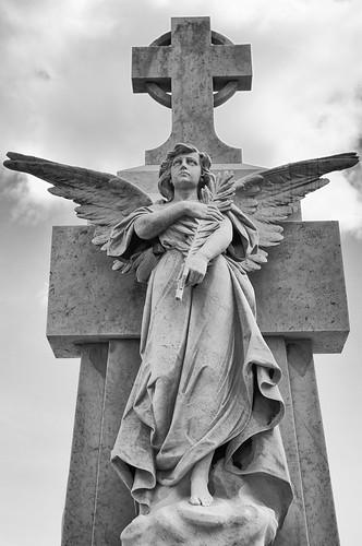 Statue of an Angel bearing an olive branch under a cross on a mausoleum