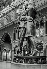 (The Meeting Place Sculpture by Paul Day) - St Pancras rail station (BW) (Olympus OMD EM5II & mZuiko 12mm f2 Prime) (1 of 1) (markdbaynham) Tags: london londoner st pancras rail station building urban metropolis omd detail em5ii csc evil mft m43 m43rd micro43 micro43rd zd mz zuiko mzuiko 12mm f2 prime microfourthirds bw sculpture paul day belgium city