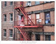 Woman on Balcony (G Dan Mitchell) Tags: brick building apartments wall woman sit balcony fireescape ladders stairs urban street photography newyork manhattan city highline park
